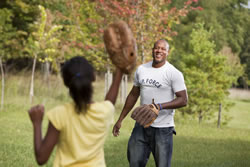 Veteran playing baseball with his daughter